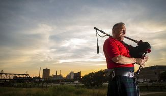 David Cohen of Davenport practices his bagpipes on the Davenport riverfront, Wednesday, July 17, 2019. Cohen moved to the Quad-Cities from Philadelphia wanting to live somewhere in a downtown loft along the Mississippi River and to focus more on his music.  (Andy Abeyta/Quad City Times via AP)