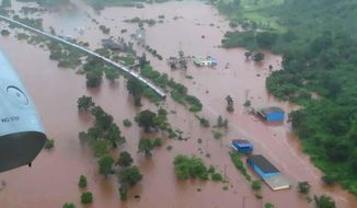 This handout photo provided by the Indian Navy shows the Mahalaxmi Express train marooned in floodwaters in Badlapur, in the western Indian state of Maharashtra, Saturday, July 27, 2019. Rescuers in India have evacuated more than 500 passengers from the train after it got stuck in floodwaters triggered by heavy rains between two stations near Mumbai. (Indian Navy via AP)