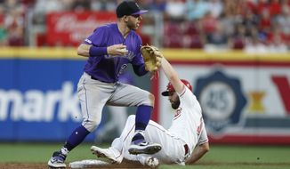 Cincinnati Reds' Jesse Winker, right, is forced out at second as Colorado Rockies shortstop Trevor Story (27) turns the double play on a Joey Votto ball during the fifth inning of a baseball game, Saturday, July 27, 2019, in Cincinnati. (AP Photo/Gary Landers)
