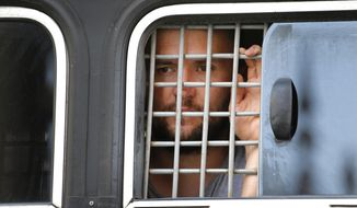 A detained protester looks out of a police bus window prior to an unsanctioned rally in the center of Moscow, Russia, Saturday, July 27, 2019. Police have established a heavy presence at the Moscow mayor's office ahead of an expected protest rally and several opposition figures have been detained. (AP Photo/Alexander Zemlianichenko)