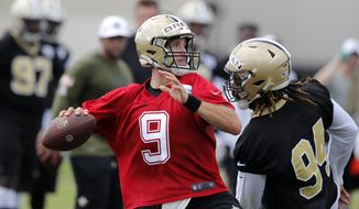 New Orleans Saints quarterback Drew Brees (9) passes under pressure from defensive end Cameron Jordan (94) during training camp at their NFL football training facility in Metairie, La., Friday, July 26, 2019. (AP Photo/Gerald Herbert)