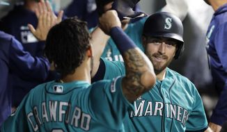 Seattle Mariners' Tom Murphy, right, is greeted by J.P. Crawford, left, after Murphy hit a game-tying two-run home run during the seventh inning of a baseball game against the Detroit Tigers, Friday, July 26, 2019, in Seattle. (AP Photo/Ted S. Warren)