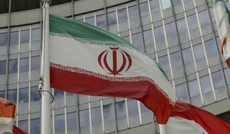"""The Iranian flag waves outside of the UN building that hosts the International Atomic Energy Agency, IAEA, office inside in Vienna, Austria, Wednesday, July 10, 2019. President Donald Trump's """"maximum pressure"""" campaign against Iran is at a crossroads. His administration is trying to decide whether to risk stoking international tensions even more by ending one of the last remaining components of the 2015 nuclear deal. (AP Photo/Ronald Zak) **FILE**"""