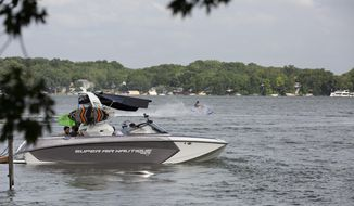 In this July 19,2019, photo a wakeboat pulls away from a dock on Lake Minnetonka in Mound, Minn. (Christine T. Nguyen/Minnesota Public Radio via AP)