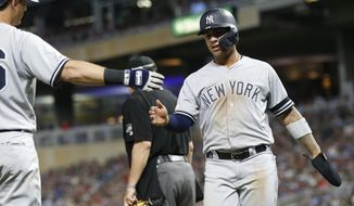 New York Yankees' DJ LeMahieu, left, congratulates Gleyber Torres after he scored on a hit by New York Yankees' Mike Tauchman in the sixth inning of a baseball game against the Minnesota Twins, Monday, July 22, 2019, in Minneapolis. The Twins won 8-6. (AP Photo/Jim Mone)