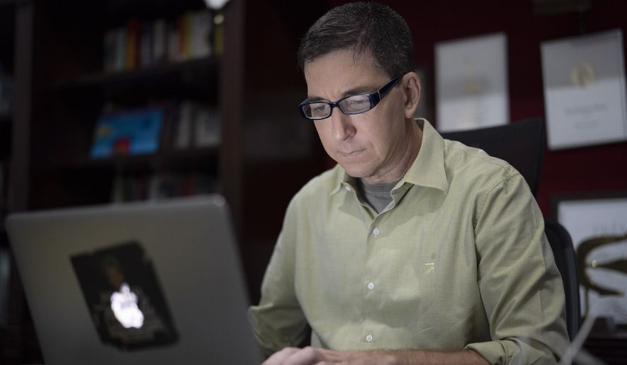 In this July 10, 2019 photo, U.S. journalist Glenn Greenwald checks his news website at his home in Rio de Janeiro, Brazil. Greenwald, an attorney-turned-journalist who has long been a free-speech advocate, has found himself at the center of the first major test of press freedom under Brazil's President Jair Bolsonaro, who took office on Jan. 1 and has openly expressed nostalgia for Brazils 1964-1985 military dictatorship, a period when newspapers were censored and some journalists tortured. (AP Photo/Leo Correa)