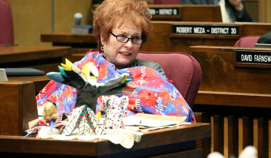 "FILE - In this May 3, 2018, file photo State Sen. Sylvia Allen keeps warm during a late-night session as the Arizona Legislature prepared to adjourn for the year in Phoenix. The veteran Arizona legislator is apologizing while defending herself from criticism for comments she made on immigration and birth rates. The Phoenix New Times posted audio of a July 15, 2019, speech during which Allen said a flood of immigration and low birth rates among whites amid a lack of cultural assimilation mean ""we're going to look like South American countries very quickly."" The Republican from Snowflake, Arizona, who is white, also said the U.S. has to regulate immigration so the country can provide jobs, education, health care and other needs.   (AP Photo/Bob Christie, File)"