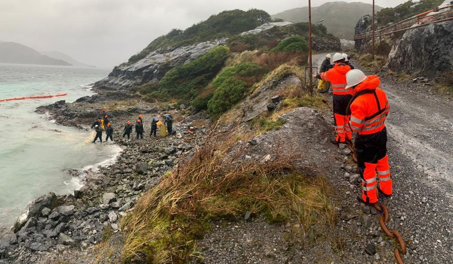 In this photo distributed by the Chile navy, sailors work to contain damage from an oil spill, on Guarello Island in Chile, Sunday, July 28, 2019. Chile's navy on Sunday confirmed the spillage of 40,000 liters of diesel oil into the sea in a remote and pristine area of the South American country's Patagonia and said it is working to mitigate the effects. (Chile navy via AP)
