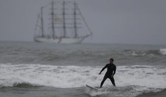 A surfer slides off a dying wave as he surfs in front of the BUP Union naval teaching ship, which was carrying the Pan Am Games torch, off the coast of Lima, Peru, Friday, July 26, 2019. In the Peruvian capital, where dozens of schools teach locals and tourists from around the world how to ride the waves at beaches with Hawaiian names, professional surfers from across the Americas are preparing to compete when the sport is featured for the first time in the Pan Am Games.(AP Photo/Rebecca Blackwell)