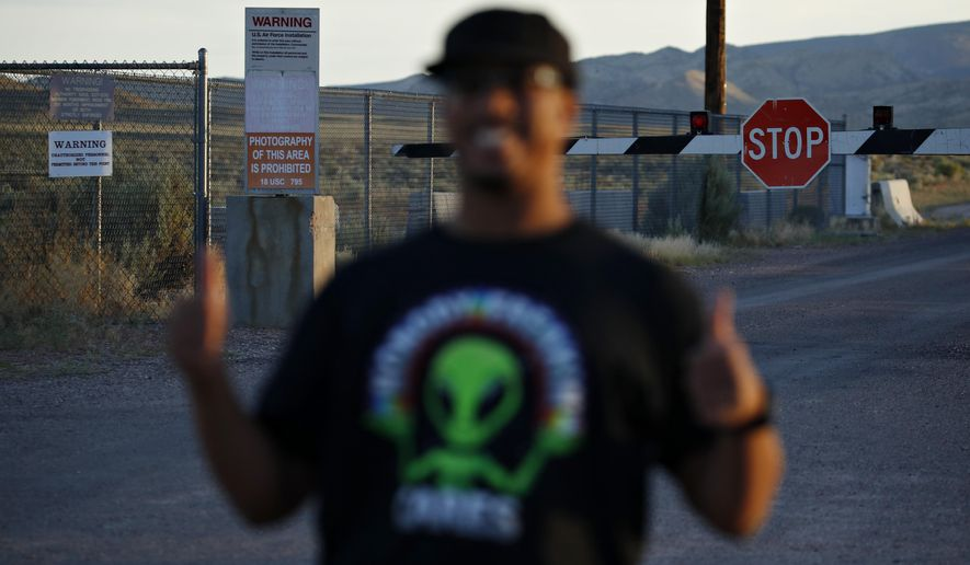 """In this July 22, 2019, file photo, Stan Evans poses as he has his picture taken while visiting an entrance to the Nevada Test and Training Range near Area 51 outside of Rachel, Nev. The U.S. Air Force has warned people against participating in an internet joke suggesting a large crowd of people """"storm Area 51,"""" the top-secret Cold War test site in the Nevada desert. (AP Photo/John Locher)"""