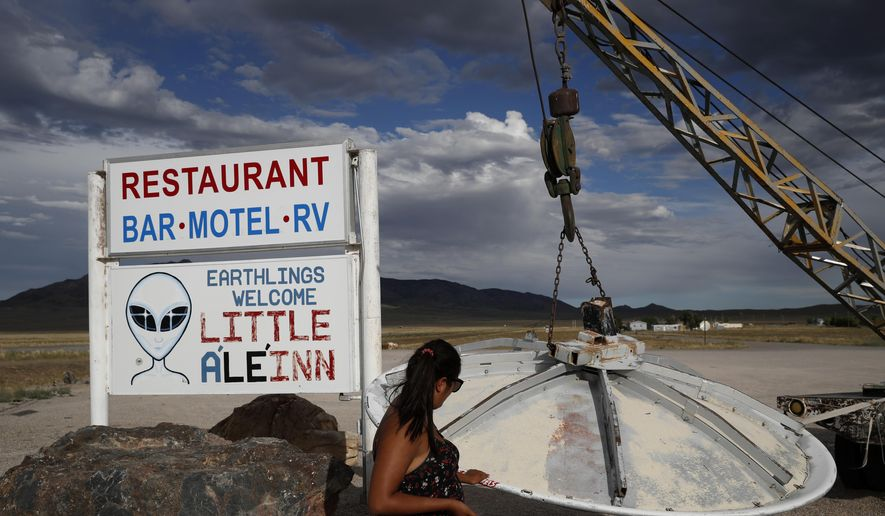 In this July 22, 2019, file photo, Grace Capati looks at a UFO display outside of the Little A'Le'Inn, in Rachel, Nev., the closest town to Area 51. (AP Photo/John Locher) ** FILE **