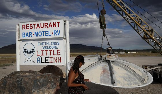 """In this July 22, 2019 photo, Grace Capati looks at a UFO display outside of the Little A'Le'Inn, in Rachel, Nev., the closest town to Area 51. The U.S. Air Force has warned people against participating in an internet joke suggesting a large crowd of people """"storm Area 51,"""" the top-secret Cold War test site in the Nevada desert. (AP Photo/John Locher)"""