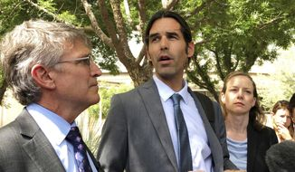 FILE - In this June 11, 2019, file photo, Scott Warren, center, speaks outside federal court, in Tucson, Ariz., after a mistrial was declared in the federal case against him. Unsealed court documents detail the way federal authorities began investigating an Arizona humanitarian group that drops off water for migrants in the desert, eventually resulting in felony trial of one of its volunteers. They deal with the arrest of Warren, of Ajo, Ariz., who was tried on conspiracy, harboring and transporting immigrant charges in June. The jury couldn't agree on a verdict, and a new trial has been scheduled for November. (AP Photo/Astrid Galvan, File)
