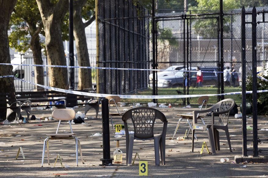 Yellow evidence markers are placed next to chairs at a playground in the Brownsville neighborhood in the Brooklyn borough of New York, Sunday, July 28, 2019. Police said, one man was killed and at least 11 others were injured in a shooting late Saturday night at the park. (AP Photo/Mark Lennihan)