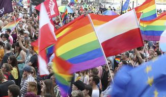 People gather to show support for the LGBT community and to show solidarity with the LGBT rights march that was attacked by far-right extremists last week in the city of Bialystok, in front of the Palace of Culture and Science, in Warsaw, Poland, Saturday, July 27, 2019.  Similar rallies of solidarity were held in other Polish cities. (AP Photo/Czarek Sokolowski)