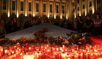 Candles are lit outside the interior ministry building in memory of a 15-year-old girl, raped and killed in southern Romania, after police took 19 hours from the moment she called the country's emergency hotline to intervene, in Bucharest, Romania, Saturday, July 27, 2019. Thousands of people took part Saturday evening in Bucharest in a march protesting the handling of the case, blaming Romanian officials for negligence, incompetence and a lack of empathy. (AP Photo/Andreea Alexandru)