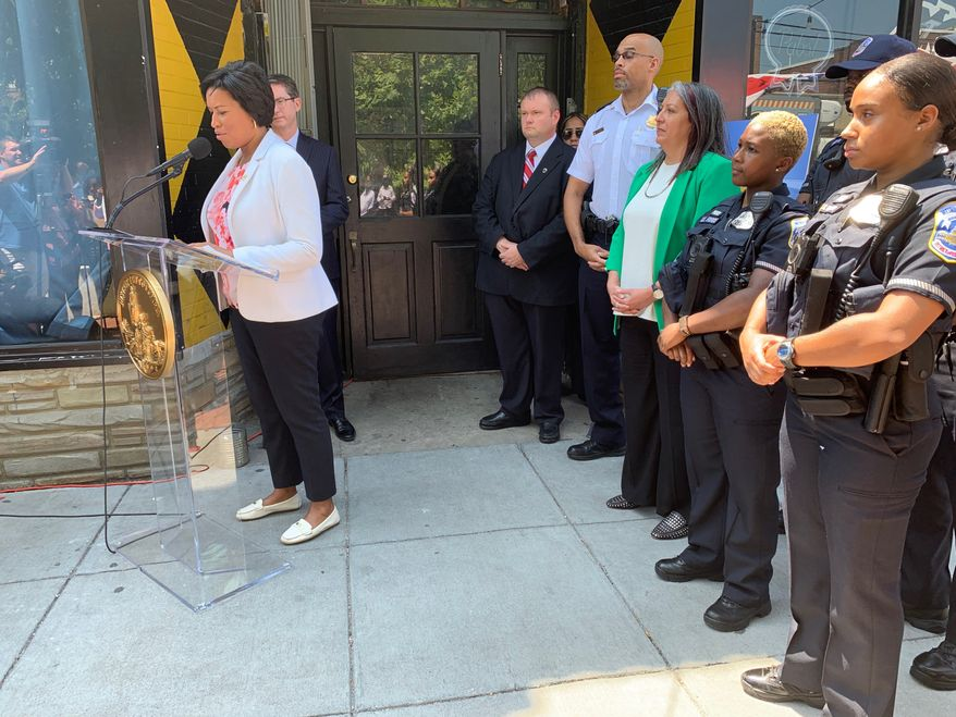 D.C. Mayor Muriel Bowser urges residents, businesses and nonprofit groups to participate in the city's Private Security Camera System Incentive Program outside of Jackie Lee's bar in Northwest on Monday. The bar was the site of a drive-by shooting on New Year's Eve. The program aims to reduce crime and catch criminals using surveillance cameras in neighborhoods. (Ximena Bustillo/ The Washington Times)