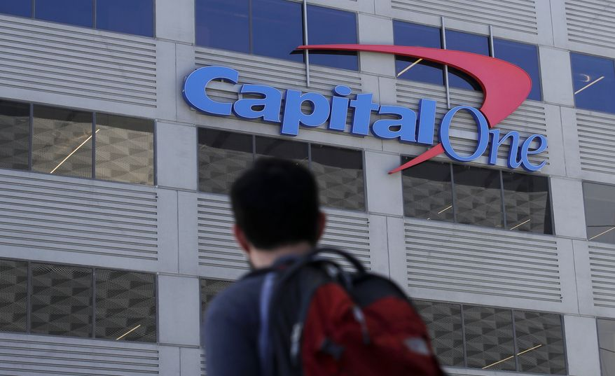 In this July 16, 2019, file photo, a man walks across the street from a Capital One location in San Francisco. Capital One says a hacker got access to the personal information of over 100 million individuals applying for credit. The McLean, Virginia-based bank said Monday, July 29, it found out about the vulnerability in its system July 19 and immediately sought help from law enforcement to catch the perpetrator. (AP Photo/Jeff Chiu)