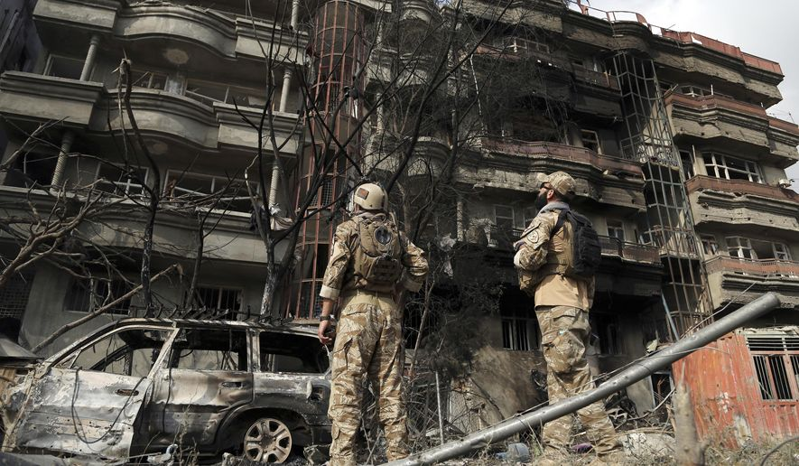 Afghan security forces stand guard at the site of Sunday's attack in Kabul, Afghanistan, Monday, July 29, 2019. A complex attack against the office of the president's running mate and a former chief of intelligence service Amrullah Saleh on Sunday in the capital Kabul, killed scores of people, an official said on Monday. (AP Photo/Rahmat Gul)