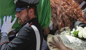 Carabinieri officer Mario Cerciello Rega's wife, Rosa Maria, right, follows the coffin containing the body of her husband during his funeral in his hometown of Somma Vesuviana, near Naples, southern Italy, Monday, July 29, 2019. Two American teenagers were jailed in Rome on Saturday as authorities investigate their alleged roles in the fatal stabbing of the Italian police officer on a street near their hotel. (AP Photo/Andrew Medichini)