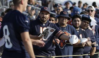 Chicago Bears fans wait for an autograph from kicker Elliott Fry (8) during an NFL football training camp in Bourbonnais, Ill., Saturday, July 27, 2019. (AP Photo/Nam Y. Huh)