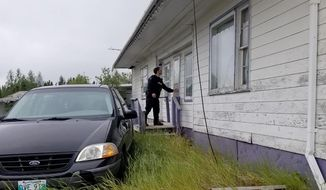 In this recent photo provided by the Royal Canadian Mounted Police, RCMP officers canvas homes and buildings in the Gillam, Manitoba area, as they continue to search for two teenagers being sought in the killings of three people in northern British Columbia. (Royal Canadian Mounted Police via AP)