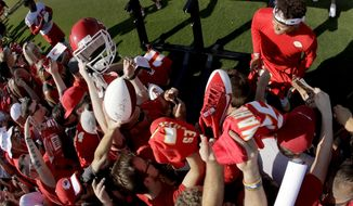 Kansas City Chiefs quarterback Patrick Mahomes, top right, gives autographs at NFL football training camp Saturday, July 27, 2019, in St. Joseph, Mo. (AP Photo/Charlie Riedel)