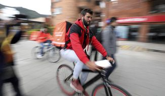 Venezuelan courier Samuel Romero, 21, takes an order to a Rappi customer on his bicycle in Bogota, Colombia, Tuesday, July 9, 2019. In a 15-hour workday Romero hopes to make around $15, the equivalent of Venezuela's monthly minimum wage but barely enough to get by in costlier Colombia. (AP Photo/Fernando Vergara)