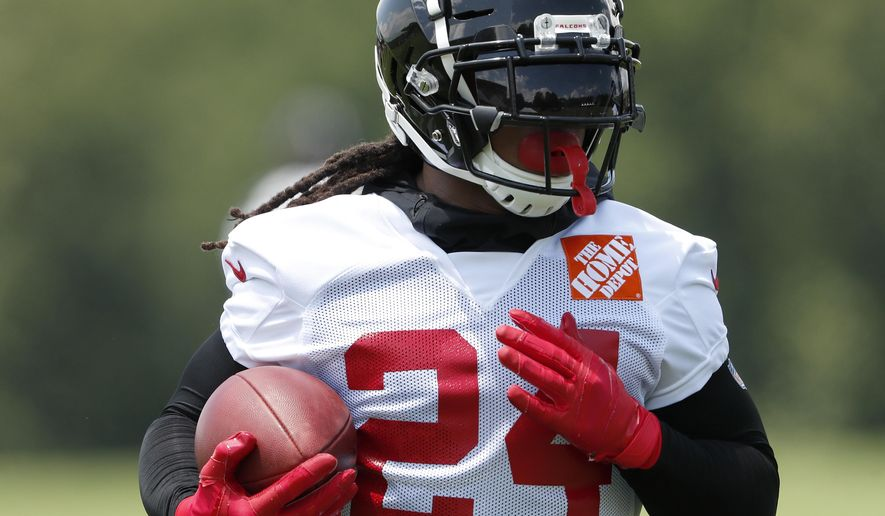 """FILE - In this Tuesday, June 11, 2019, file photo, Atlanta Falcons running back Devonta Freeman (24) runs during an NFL football practice in Flowery Branch, Ga.  When Atlanta Falcons coach Dan Quinn calls running back Devonta Freeman a """"multiplier"""" he is talking about Freeman making every other player on the offense better. That makes Freeman's health an obvious key after he was limited by injuries to two games in 2018. (AP Photo/John Bazemore, File)"""