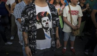 Demonstrators demand the resignation of Guatemalan President Jimmy Morales, one wearing a T-shirt of Morales as a clown, outside the Presidential House in Guatemala City, Saturday, July 27, 2019. Demonstrators are protesting an agreement their government signed with Washington to require migrants passing through the Central American country to seek asylum there, rather than pushing on to the U.S. Before becoming president, Morales was a professional comedian. (AP Photo/ Oliver de Ros)