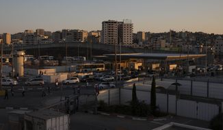 In this Thursday, July 11, 2019, photo, cars pass the Qalandia crossing between the West Bank city of Ramallah and Jerusalem. (AP Photo/Sebastian Scheiner)