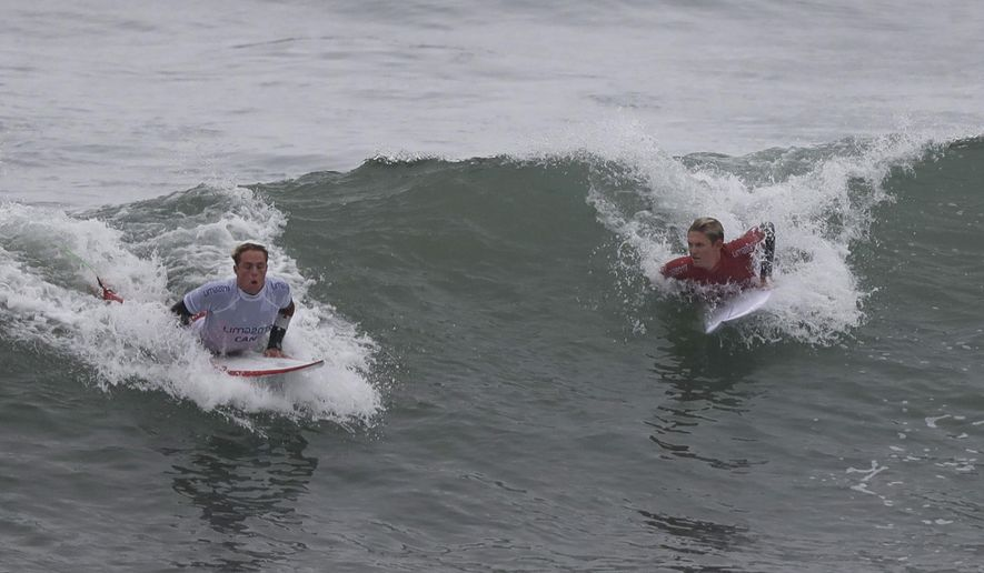 Canada's Cody Young, left, and Kevin Schulz of the United States, compete in the men's open surfing main round 1, during the Pan American Games on Punta Rocas beach in Lima, Peru, Monday, July 29, 2019. (AP Photo/Silvia Izquierdo)