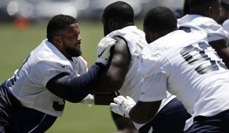 FILE - In this May 28, 2019, file photo, Los Angeles Rams defensive linemen, including Aaron Donald, left, go through drills during an NFL football training camp in Thousand Oaks, Calif. Donald is participating in his first training camp since 2016 after holding out for the past two summers in search of a new contract. (AP Photo/Marcio Jose Sanchez, File)