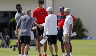 New Orleans Saints head coach Sean Payton, left with back facing camera, greets NBA basketball New Orleans Pelicans draft picks Zion Williamson, left, Jaxson Hayes, center, and head coach Alvin Gentry during training camp at their NFL football training facility in Metairie, La., Friday, July 26, 2019. With them are Saints general manager Mickey Loomis, center with back to camera, and former Saints head coach Jim Mora, right. (AP Photo/Gerald Herbert)