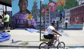 "A boy rides his bicycle Monday, July 29. 2019 after volunteering to paint a mural outside the New Song Community Church in the Sandtown section of Baltimore. Rep. Elijah Cummings, who represents the 7th Congressional District of Maryland, said he hoped President Trump would ""see the beautiful neighborhoods of our city."" (AP Photo/Julio Cortez) **FILE**"