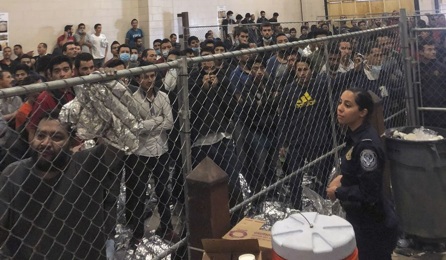 In this July 12, 2019 file photo, men stand in a U.S. Immigration and Border Enforcement detention center in McAllen, Texas, during a visit by Vice President Mike Pence.  Immigration lawyers say a pattern has repeated itself for several weeks in migrant detention facilities along the border. Immigrants are being detained in packed cells only to be transferred out within hours once the government is sued on their behalf. (Josh Dawsey/The Washington Post via AP, Pool)