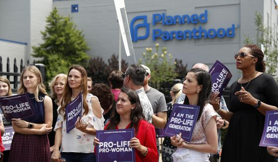 FILE - In this June 4, 2019, file photo, Anti-abortion advocates gather outside the Planned Parenthood clinic in St. Louis. Planned Parenthood and the American Civil Liberties Union filed a lawsuit Tuesday, July 30, against the state of Missouri to stop a law that bans abortions beyond the eighth week of pregnancy from taking effect Aug. 28. (AP Photo/Jeff Roberson, File)