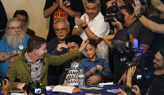 """Journalist Glenn Greenwald, left, reaches out to pat his son's head during an act in support of Greenwald at the Brazilian Press Association headquarters in Rio de Janeiro, Brazil, Tuesday, July 30 , 2019. Brazil's president has raised the possibility of jail for Greenwald a few days after members of his party said the American's Brazil-based internet publication was """"aligned with criminal hackers"""" for reporting on hacked phone calls. (AP Photo/Ricardo Borges)"""