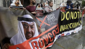 Demonstrators hold banners as they demonstrate against Sheikh Mohammed bin Rashid al-Maktoum outside The High Court in London, Tuesday, July 30, 2019.  Sheikh Mohammed bin Rashid al-Maktoum has made an application to divorce his wife of 15 years, Princess Haya Bint al-Hussein, in the Family Court Division of the High Court. (AP Photo/Kirsty Wigglesworth)