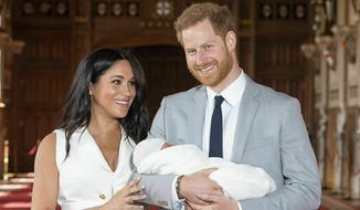 In this Wednesday, May 8, 2019, file photo shows Britain's Prince Harry and Meghan, the Duchess of Sussex, during a photocall with their newborn son in St. George's Hall at Windsor Castle, England. (Dominic Lipinski/Pool via AP, file)