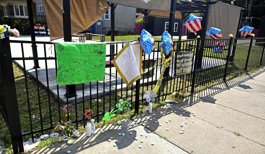 A memorial stands at 75th Street and Stewart Avenue in Chicago, where two women were slain in a drive-by shooting Friday night. (John Alexander/Chicago Sun-Times via AP)