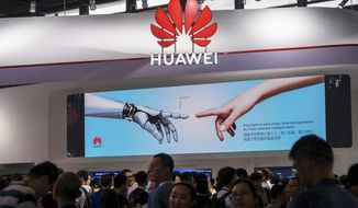 In this June 26, 2019, photo, visitors tour the Huawei pavilion at the Mobile World Congress in Shanghai, China. Chinese tech giant Huawei said Tuesday, July 30, 2019 its global sales rose by double digits in the first half of this year despite being placed on a U.S. security blacklist but said it will face tougher conditions. (Chinatopix via AP)