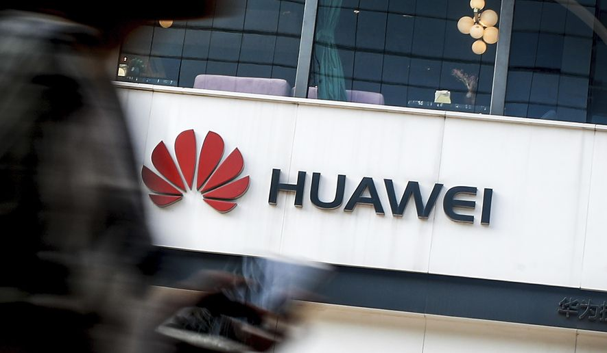 A woman walks by a Huawei retail store in Beijing, Tuesday, July 30, 2019. (AP Photo/Andy Wong) ** FILE **