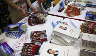 Copies of the book on the governance of Chinese President Xi Jinping are displayed with booklets promoting Xinjiang during a press conference by Shohrat Zakir, chairman of China's Xinjiang Uighur Autonomous Region, at the State Council Information Office in Beijing, Tuesday, July 30, 2019. The governor of China's far-northwestern region of Xinjiang is defending controversial re-education centers in the region as an effective deterrent against terrorism and religious extremism. (AP Photo/Andy Wong)