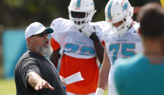 Miami Dolphins new offensive line coach Dave DeGuglielmo, left, runs players through drills at the teams NFL football training camp, Tuesday, July 30, 2019 in Davie, Fla. (AP Photo/Wilfredo Lee)