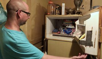 """In this Monday, July 29, 2019 photo, Adam Smith peers into his mother's freezer in St. Louis, where he found the remains of an infant wrapped in a box she kept there for more than 40 years. Police said in a news release that the death is being investigated as """"suspicious"""" pending an autopsy. Smith says he was going through his mom's belongings on Sunday after she died on July 21, at the age of 68 from lung cancer. (Christine Byers/St. Louis Post-Dispatch via AP)"""