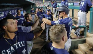 Seattle Mariners' Kyle Seager, right, is congratulated in the dugout after scoring on a Tom Murphy single during the seventh inning of the team's baseball game against the Texas Rangers in Arlington, Texas, Tuesday, July 30, 2019. (AP Photo/Tony Gutierrez)