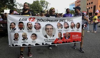 """Protesters hold a banner featuring resigned Gov. Ricardo Rosselló, center, amid other politicians that reads in Spanish """"The 12 disciples of evil. Them too."""" as they demand the resignation of Justice Secretary Wanda Vazquez outside the Department of Justice in San Juan, Puerto Rico, Monday, July 29, 2019. Less than four days before Gov. Ricardo Rosselló steps down, no one knows who will take his place and his constitutional successor Wanda Vázquez said Sunday that she didn't want the job. (AP Photo/Brandon Cruz González)"""