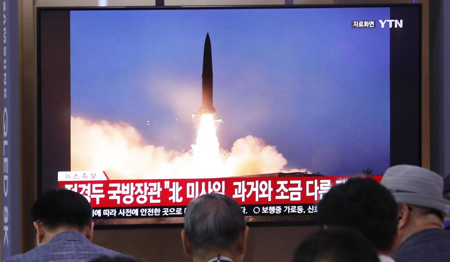 """People watch a TV showing a file image of North Korea's missile launch during a news program at the Seoul Railway Station in Seoul, South Korea, Wednesday, July 31, 2019. North Korea on Wednesday fired several unidentified projectiles off its east coast, South Korea's military said, less than a week after the North launched two short-range ballistic missiles into the sea in a defiance of U.N. resolutions. The signs read: """"North Korea's missile is a bit different from the past."""" (AP Photo/Ahn Young-joon)"""