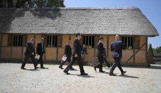 An advance team from the Secret Service walks past the reconstructed church at the Jamestown Settlement in James City County, Va. Monday, July 29, 2019, where the Virginia General Assembly will meet at 10am Tuesday to commemorate the 400th anniversary of the first representative assembly in the Western Hemisphere. President Trump is scheduled to speak Tuesday at a nearby gathering at 11am. (Bob Brown/Richmond Times-Dispatch via AP)